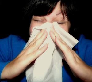 A lady sneezing in a white hankie